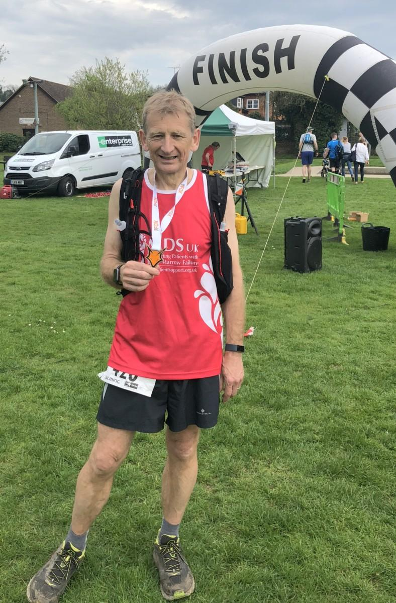Alastair after the race, with his The Fox Ultra 42K  medal at the finish line